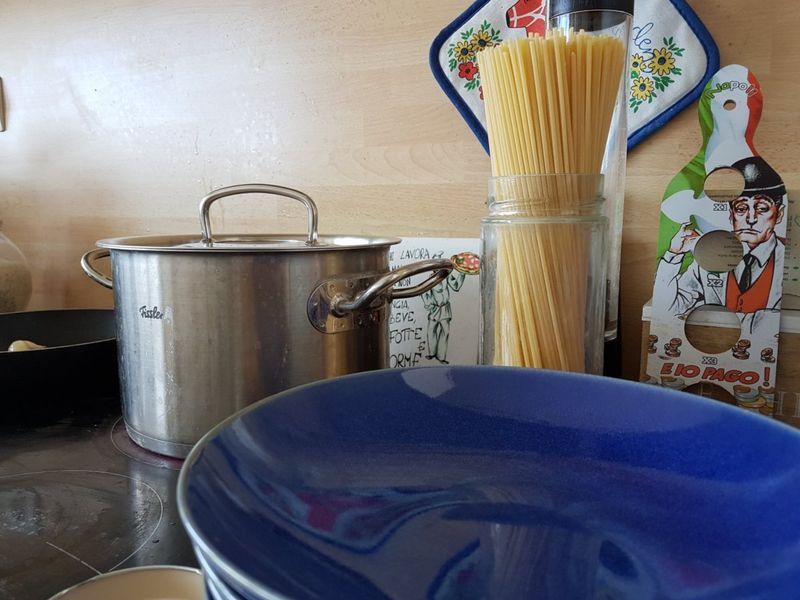 Des assiettes, une casserole et des pâtes longues